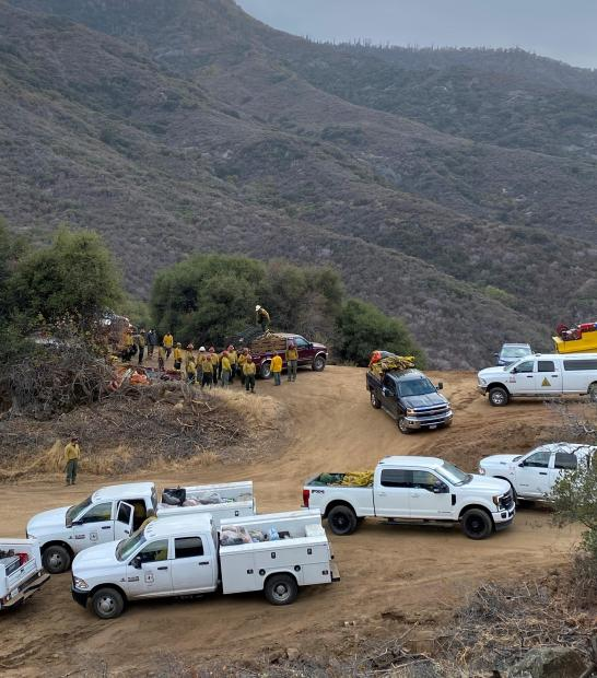 Crews and trucks move around a staging area with a mountain in the background