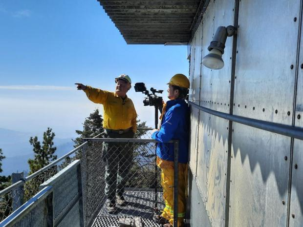 One person interviews another on top of a catwalk on a fire tower