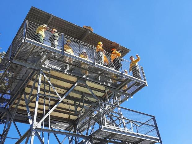 10 people wearing yellow and green clothes are standing on a catwalk of a metal fire tower