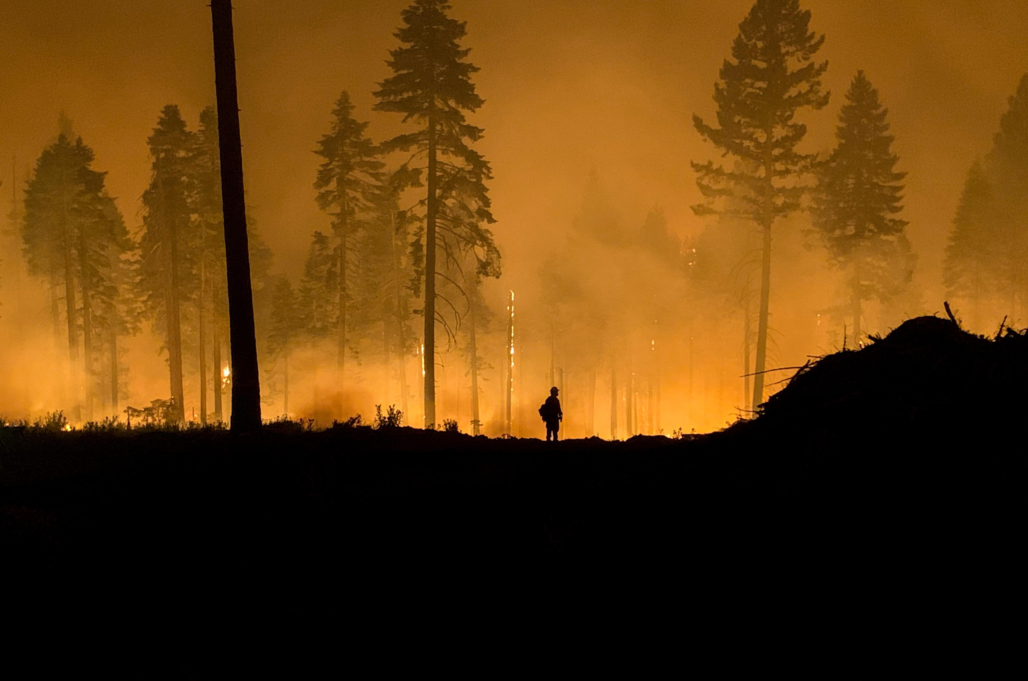 A silhouette of a firefighter on the fireline with flames in the background