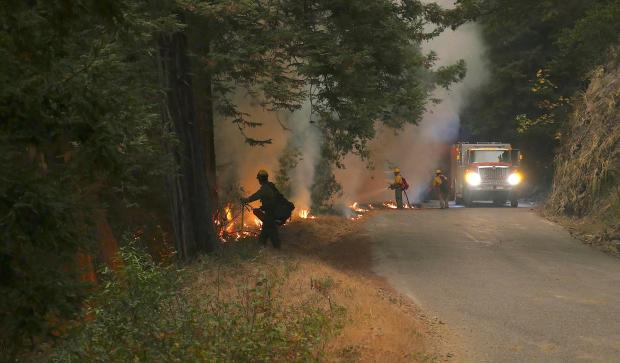 Firefighters and a fire engine are seen on a road with a fire nearby. One firefighter holds hose, another has a tool and a drip torch.