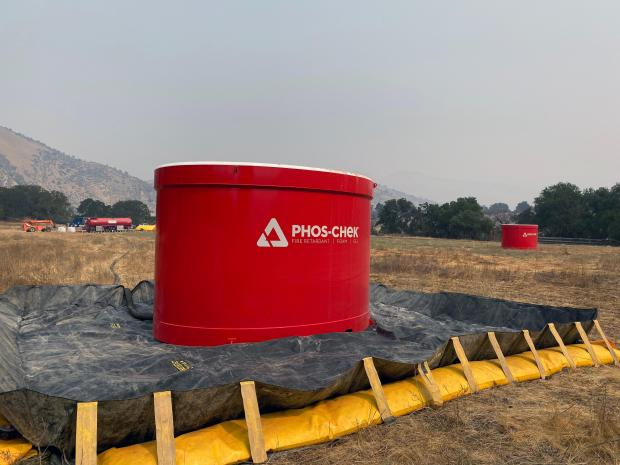 Two large, red tanks are shown in a field as part of a mobile base to supply fire retardant.