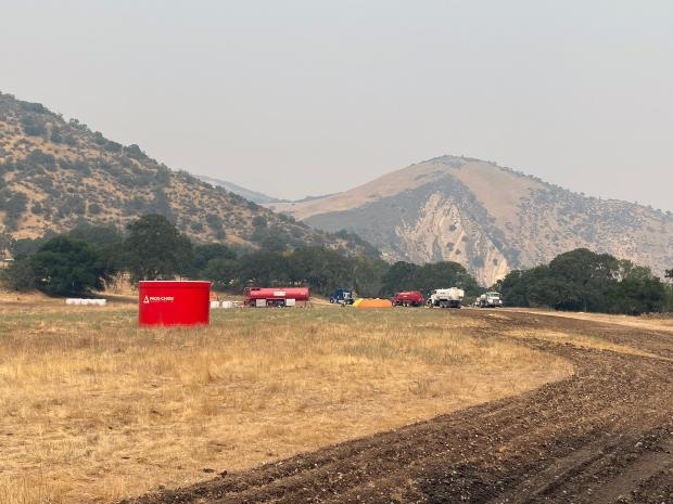 A smokey valley is shown with trucks and tanks that make up a mobile fire retardant base.