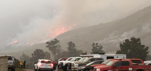 A parking lot with vehicles is seen with flames on a hillside in the distance.