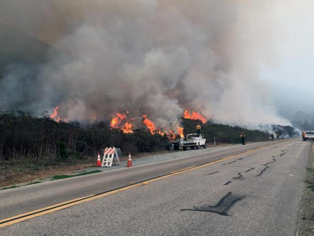 California Highway 1 is show with firefighters strung along it, watching a fire on the slope above them.
