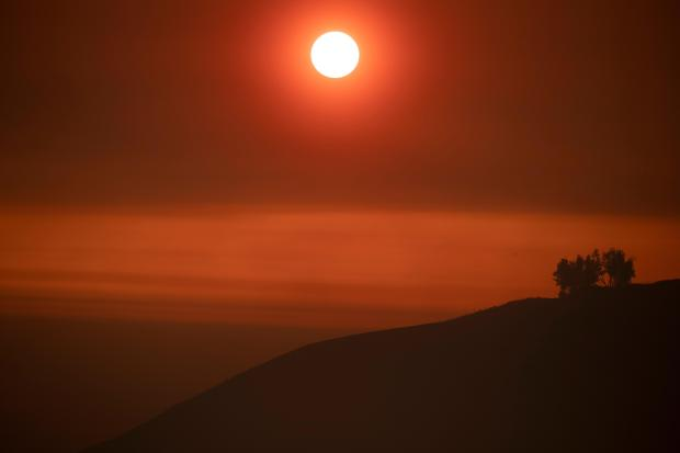 The setting sun, filtered orange through a layer of smoke, sets above the Pacific Ocean.