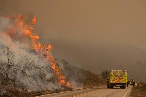 Large flames and smoke climb above vegetation on the left side of the picture, a fire engine and firefighters are shown below on the highway.