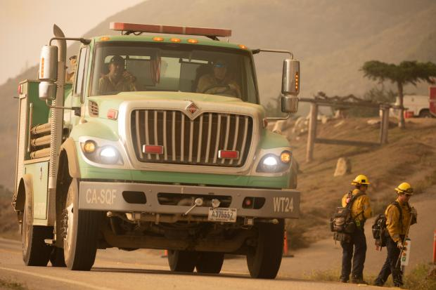 A green forest service fire engine fills the frame, a female firefighter driving with a male fireighter riding next to her.