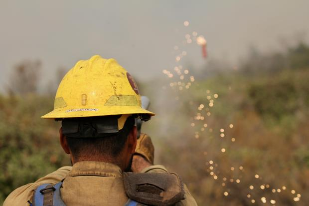 A firefighter in a helmet shoots a flare gun-type pistol. The incidiary device, trailing sparks, is seen flying toward vegetation.