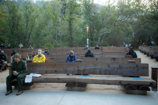 a few people sit scattered on benches observing socially distancing measures.