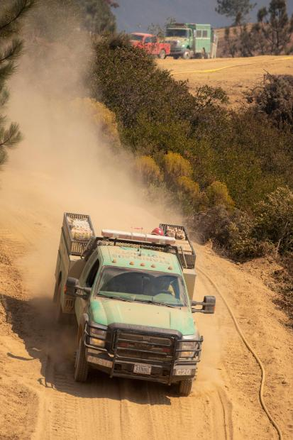 A Forest Service engine descends a dusty road.