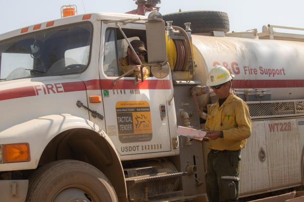 A firefighter discusses the fire with a water tender driver sitting in his truck.