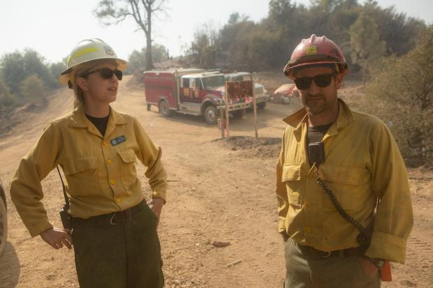 Two firefighters stand on a road with a fire engine in the background.