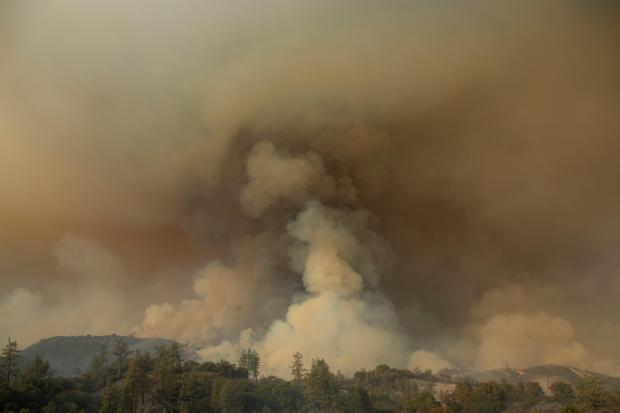 Thick smoke obscures the sky above a ridge
