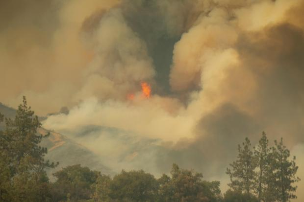 Thick smoke obscures the sky above a ridge and flames are visible in spots.