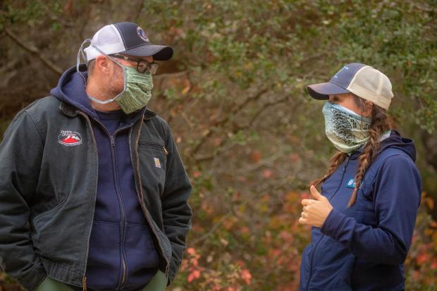 Two firefighters are shown, a man and a woman, both are wearing masks.