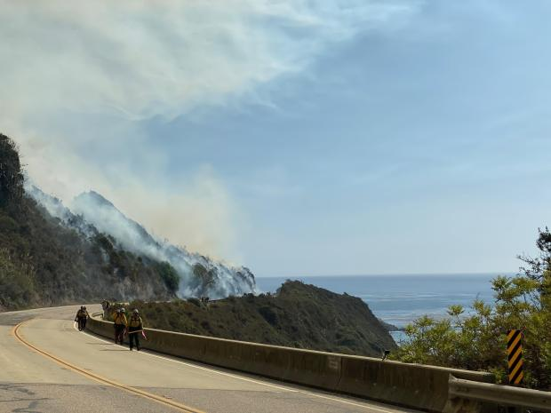 Firefighters are walking along a highway with a smoky fire behind them. The Pacific Ocean can be seen to the right.