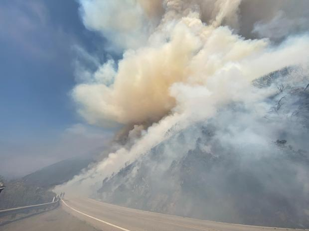 Smoke is seen billowing off a slope next to a highway.
