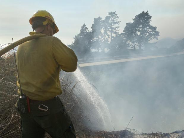 A firefighter with a hose is shown spraying water while standing amid smoke.