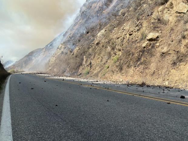 Rocks litter a highway after they were loosed by fire on the hill above.