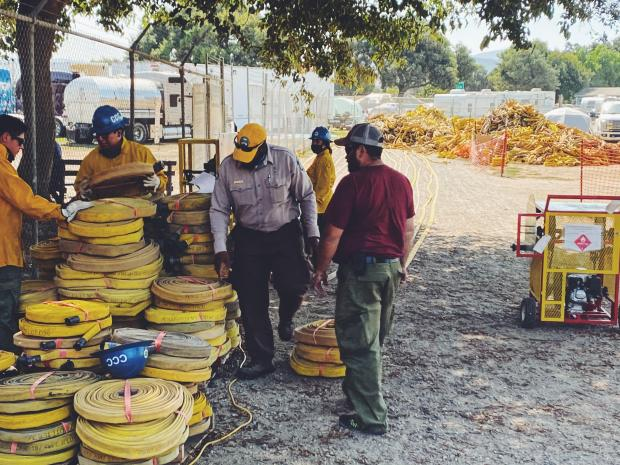 Crews at the Dolan Fire base camp work to clean and roll hoses with a large pile of hoses in the background waiting to be cleaned and rolled.
