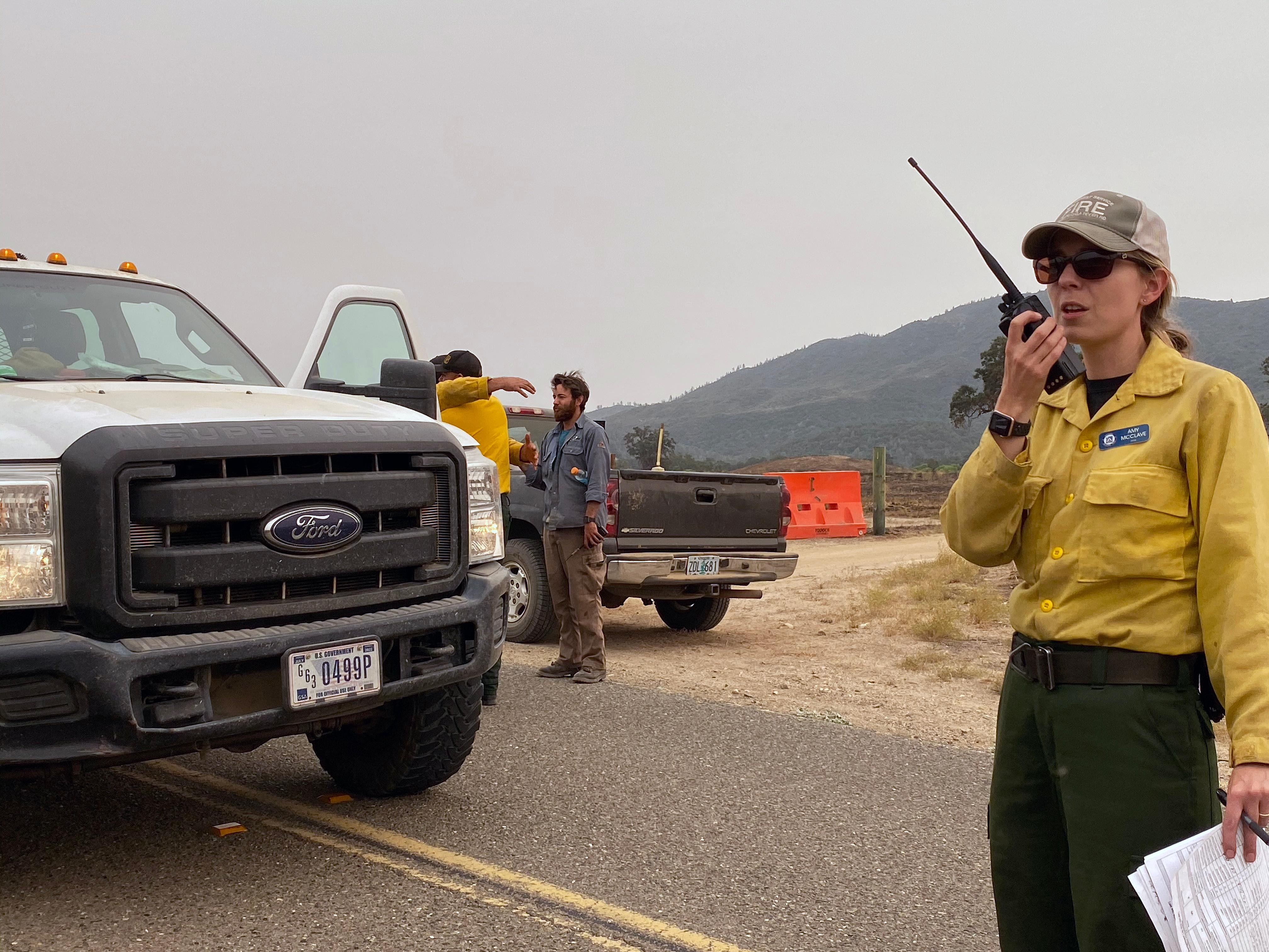 A female firefighter speaks into a radio while standing next to a truck.