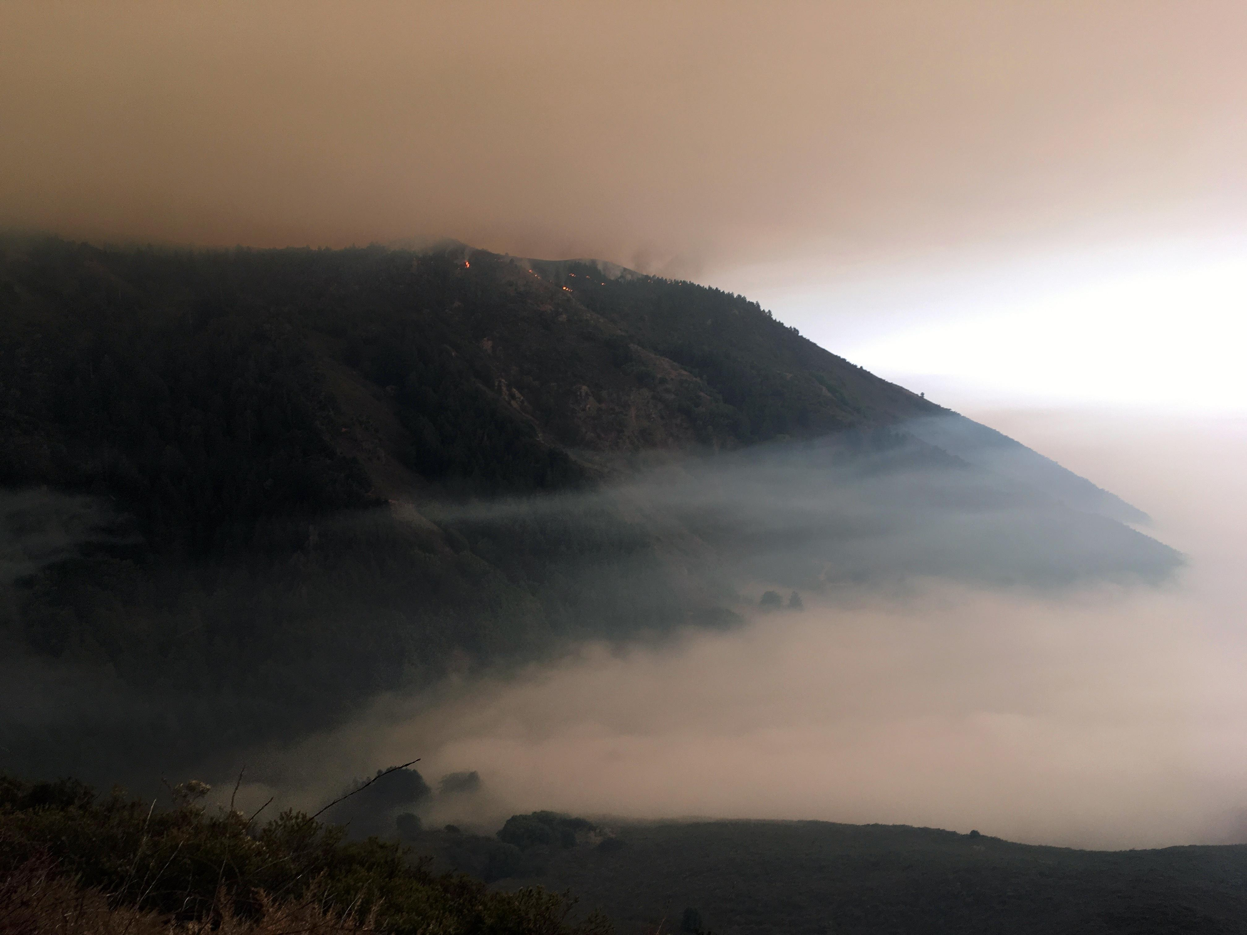 Fires dot the top of a forested ridge with the marine layer of clouds blanketing the area below.