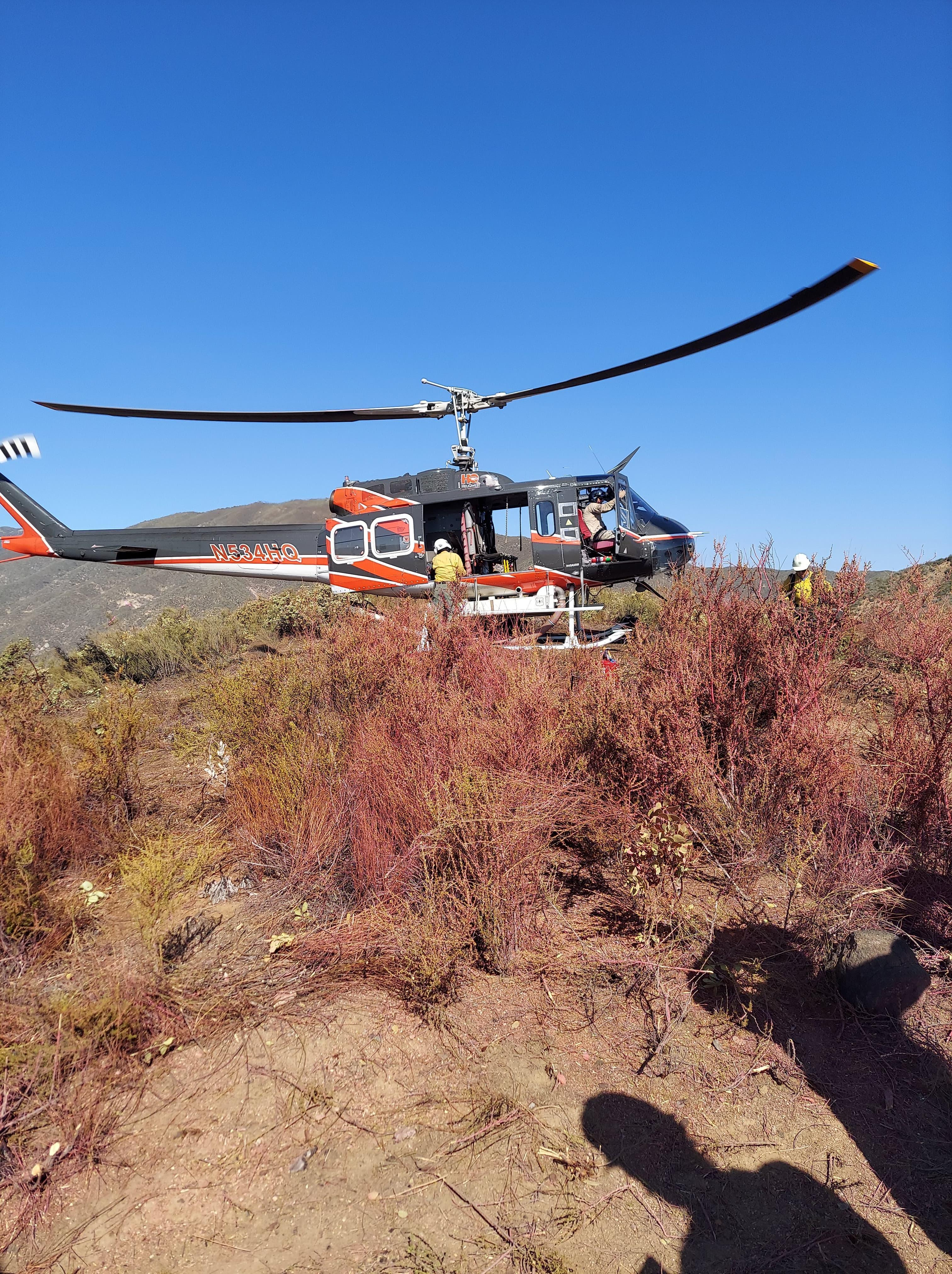 Helicopter landing on a ridge top.