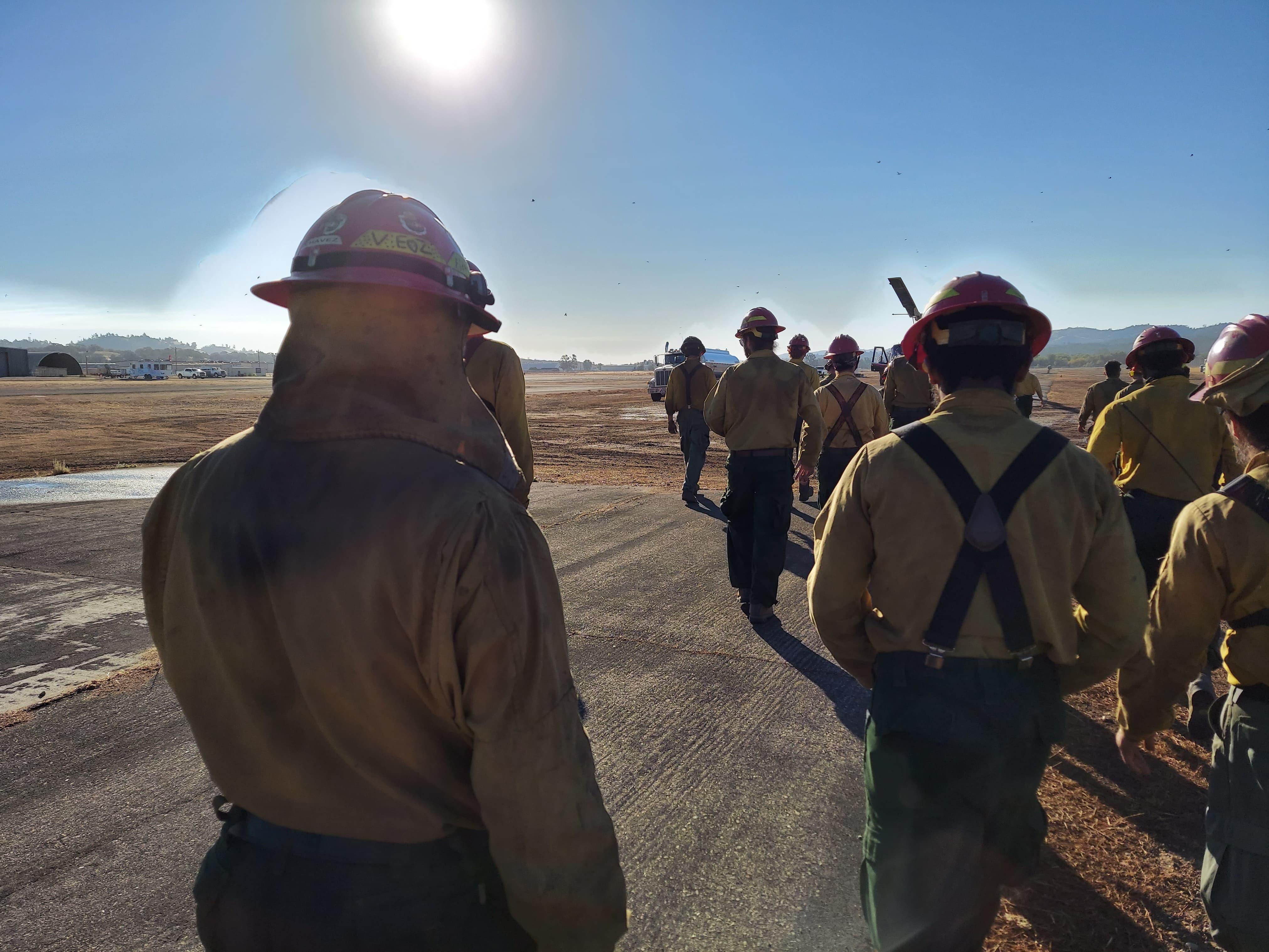 Firefighters walking towards a helicopter