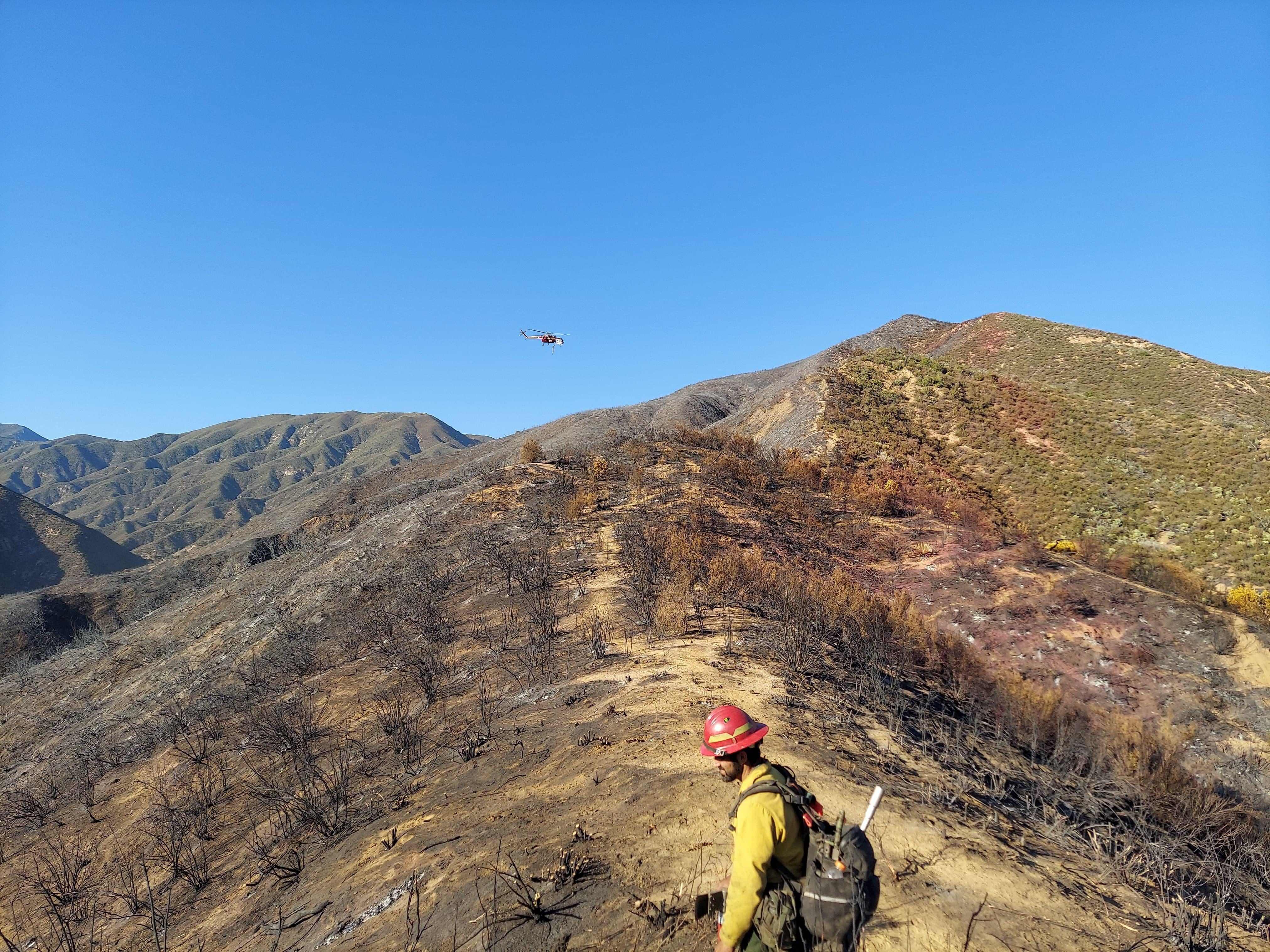 Firefighters hike the ridgeline to get to their work area for the day.