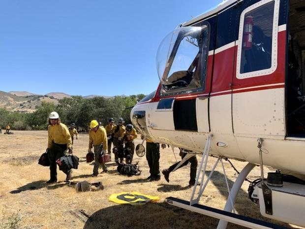 Firefighters loading in a helicopter to be dropped off closer to fire line.