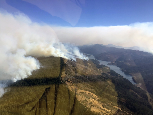 Smoke rises from a forest with a large lake on the left hand side of the photo, which was taken from a helicopter.