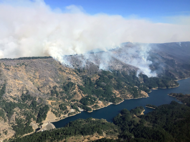 Smoke rises from a forest with a large lake at the bottom of the photo, which was taken from a helicopter.