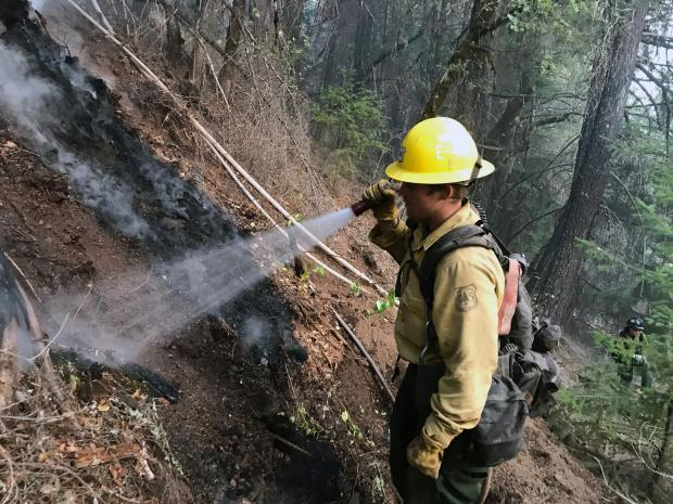 A firefighter uses a small fire hose to extinguish smoking vegetation. He is wearing a helmet and fire pack.