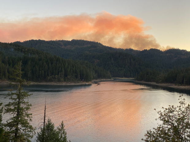 A small cloud of smoke rises over a lake and forested hills, lit up pink by the setting sun