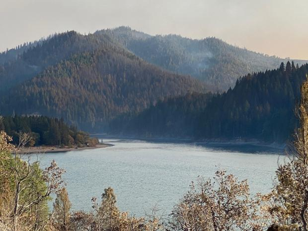 Forested hills surround a blue mountain lake, with oak trees in the foreground