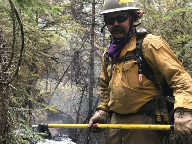 A fireighter in protective clothing, a helmet and sunglasses holds a tool. Ashes and vegetation are visible as well.