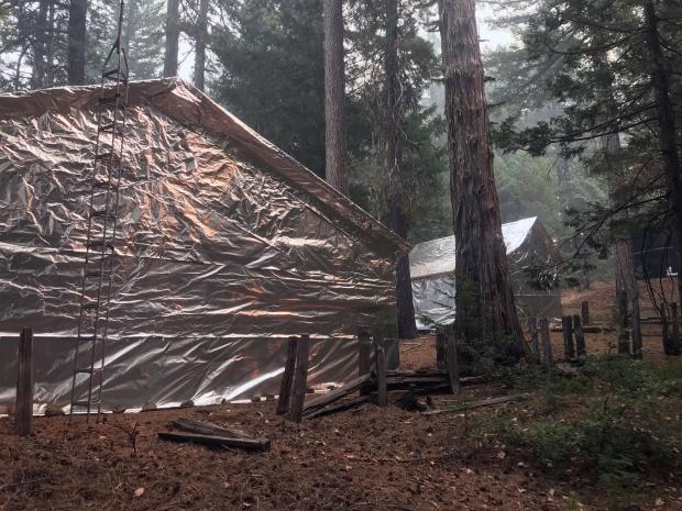 Two forest service building are shown, each wrapped in an aluminum foil like material, to protect them from heat and embers.