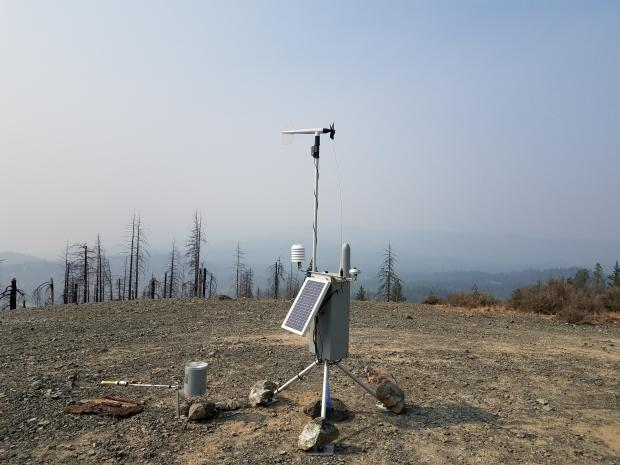 A weather station sits on top of a bare gravel-covered hill, with burned trees in the background and smoky skies