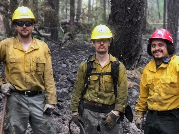 Three firefighters, in helmets and dirty yellow hardhats, pose for a picture.