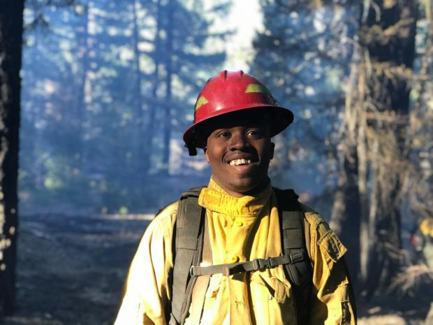 A firefighter wearing yellow nomex shirt and hardhat poses for a photo