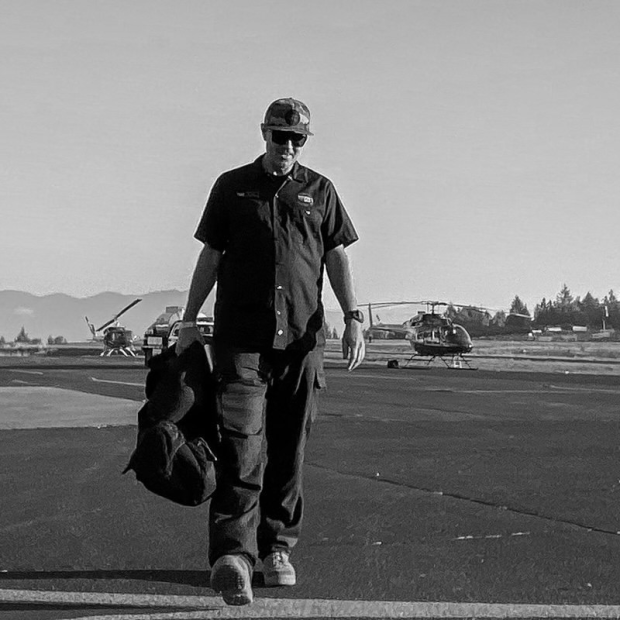 Black and white photo of Air Operations Branch Director walking across tarmac towards camera with two helicopters and fuel truck in the background