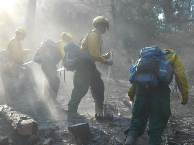 A Marine wildland firefighter stands on a steep slope with a tool in hand. Other firefighters surround him.
