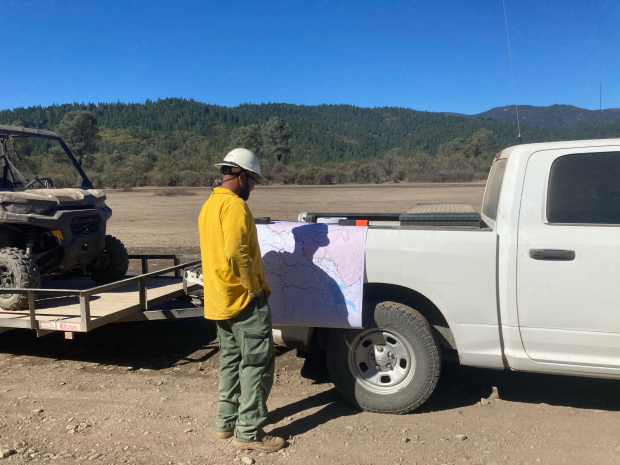Firefighter at Gravelly Spike Camp, located North of Pillsbury Lake,  looking at map suppression repair planning