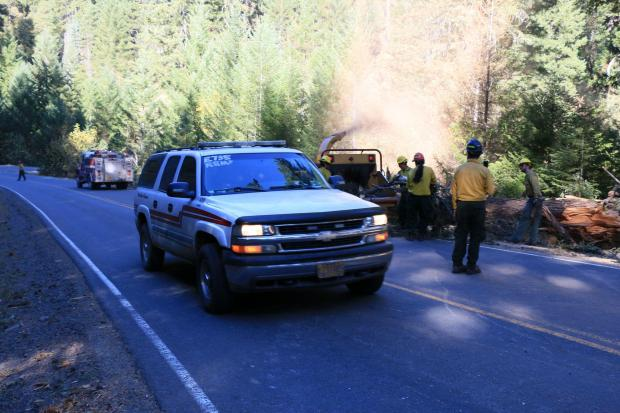 A rescue vehicle drives along a road past firefighters chipping woody debris.