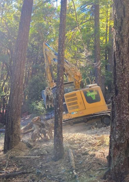 An excavator digs water bars on a dozer line near a burned area