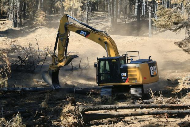 An excavator moves logs to protect dozer line against erosion.
