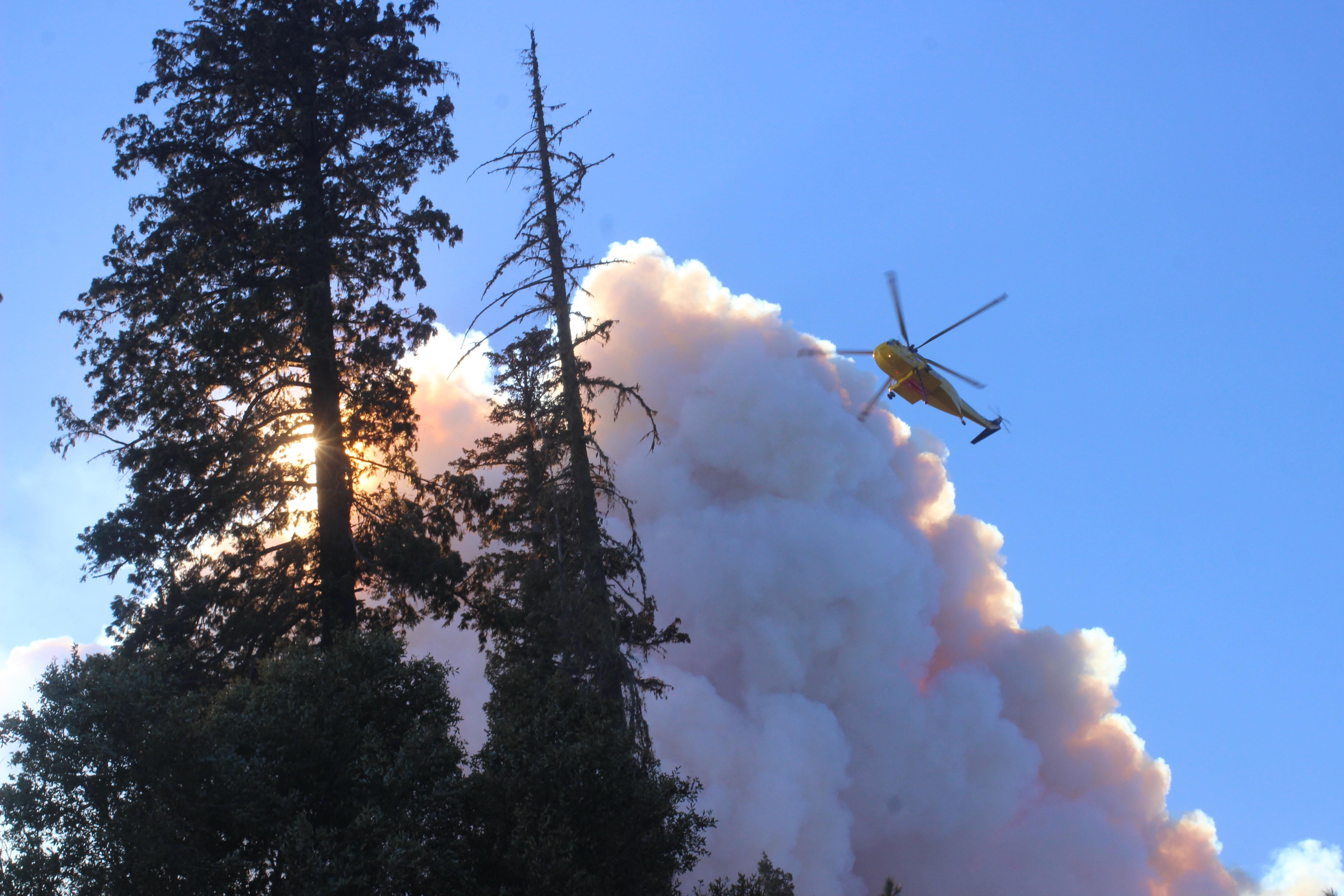 Helicopter flying near smoke plume. Photo Credit: Mike McMillan/USFS