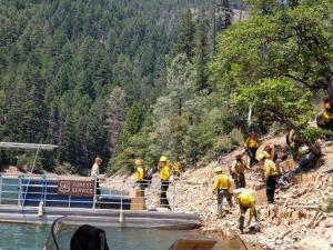 Firefighters arrive onshore after being ferried across Trinity Lake to the Captain Fire by FS Lake Recreation staff.