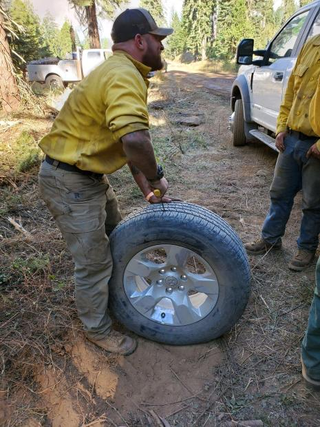 A mechanic in nomex plugs a flat tire in the field.